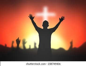 Thanksgiving concept: Silhouette people raising hands to worship God over blurred the white cross on autumn sunset background