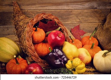 Thanksgiving cornucopia close up against a rustic wooden background