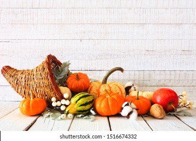 Thanksgiving cornucopia filled with autumn vegetables and pumpkins against a rustic white wood background