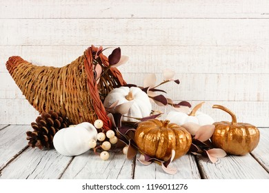 Thanksgiving cornucopia filled with white and gold pumpkins against a white wood background