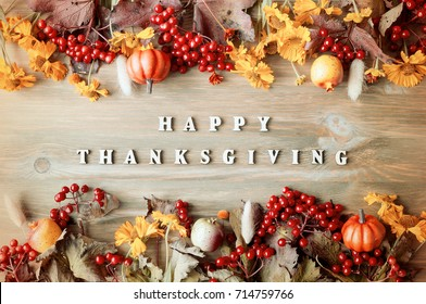 Thanksgiving day autumn background with Happy Thanksgiving letters, seasonal autumn nature berries, pumpkins, apples and flowers on the wooden background