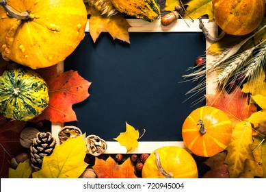 Thanksgiving day background. Autumn vegetables nuts and leaves around chalkboard. Top view with copy space.