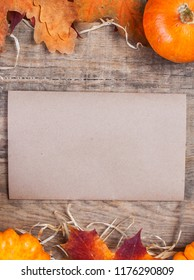 Thanksgiving Day Card with orange pumpkins and colourful leaves on wooden background