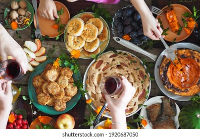 Thanksgiving day celebration concept. People take healthy homemade natural food with their hands. Guests' hands over the table set with food. A lot of food.