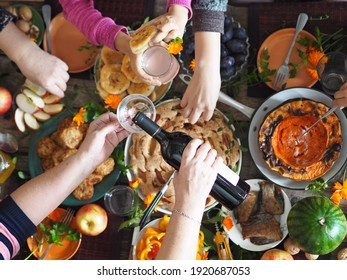 Thanksgiving day celebration concept. There is a lot of food on the wooden table. Guests pour red wine and take healthy homemade natural food with their hands.