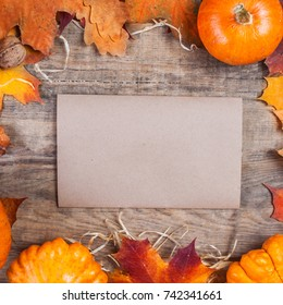 Thanksgiving Day concept -  border or frame with orange pumpkins and colourful leaves on wooden background with blank tag paper for text.