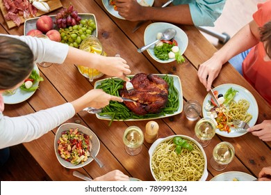 thanksgiving day, eating and leisure concept - group of people having roast chicken or turkey for dinner at table with food