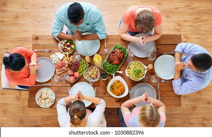 thanksgiving day, food and religious concept - group of people sitting at table and praying before meal