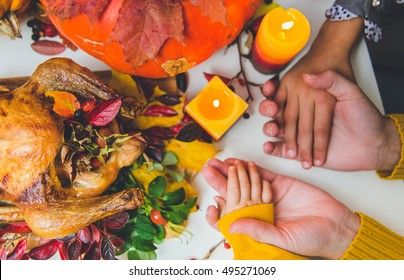 Thanksgiving day. Hands of woman, two child - caucasian boy and multi ethnic or multi race girl. Boy trying give peace of turkey. Flat view. Pumpkins, hands, candles, turkey on view.