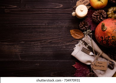 Thanksgiving decoration with cutlery and napkin on the wooden table, top view. Copy space.