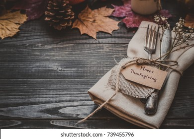 Thanksgiving decoration with cutlery and napkin on the wooden table with copy space. Selective focus.