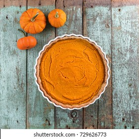 Thanksgiving dessert. Homemade rustic open pumpkin pie with small decorative pumpkins on shabby blue wooden table above view