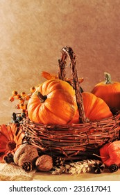 Thanksgiving - different pumpkins in rattan basket in front of brown background in candle light