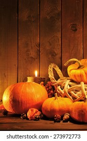 Thanksgiving - different pumpkins in rattan basket in front of old weathered wooden boards in candle light