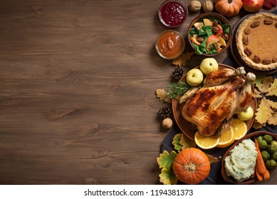 Thanksgiving dinner background with turkey and all sides dishes, pumpkin pie, fall leaves and seasonal autumnal decor on wooden background, top view, copy space.