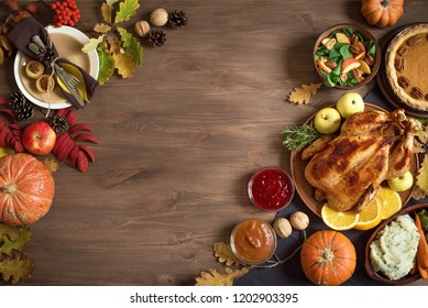 Thanksgiving dinner background with turkey and all sides dishes, pumpkin pie, fall leaves, table setting and seasonal autumnal decor, top view, copy space.