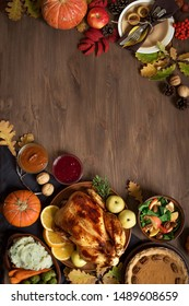 Thanksgiving dinner background with turkey and all sides dishes, pumpkin pie, fall leaves and seasonal autumnal decor on wooden table, top view, copy space.
