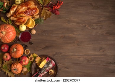 Thanksgiving dinner background with turkey, fall leaves, seasonal autumnal decor and table setting, top view, copy space.