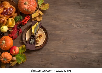 Thanksgiving dinner background with turkey, pumpkins, fall leaves, table setting and seasonal decor, top view, copy space.