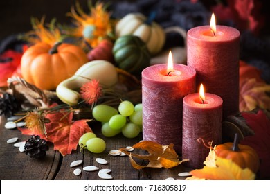 Thanksgiving dinner concept. Lit candles with pumpkins, grapes, autumn leaves and fall decorations