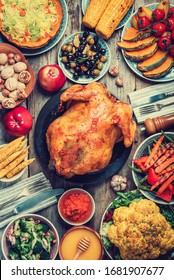 Thanksgiving dinner cooking preparation. Traditional dishes: chicken, pumpkin, corn, vegetables salads over wooden background. Top view, copy space. Autumn harvest, organic vegetables. Family dinner