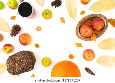 Thanksgiving dinner frame made of fall leaves, mug of coffee, bread and apples with pumpkin on white background. Flat lay, top view