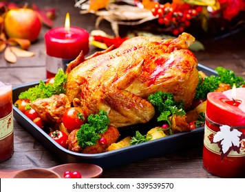 Thanksgiving Dinner. Roasted turkey garnished with Potato, Vegetables and cranberries on a rustic style table decorated with autumn leaves and candles.