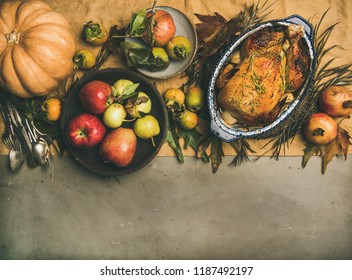 Thanksgiving dinner table. Flat-lay of roasted chicken or turkey, autumn fruit, pumpking, cutlery,leaves decoration over yellow linen table runner on grey concrete background, top view, copy space