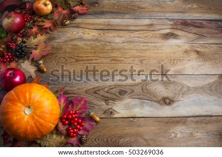 Thanksgiving  or fall background with orange pumpkins and fall leaves. Greeting card with seasonal vegetables and fruits. Copy space