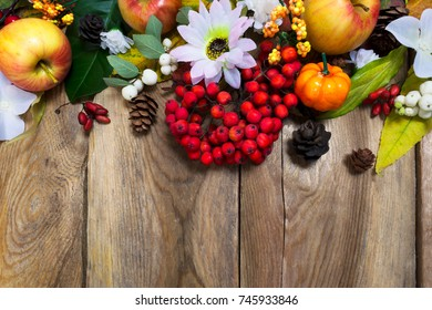 Thanksgiving or fall decoration with pumpkin, apples, autumn leaves and rowan berries on the rustic wooden background, copy space