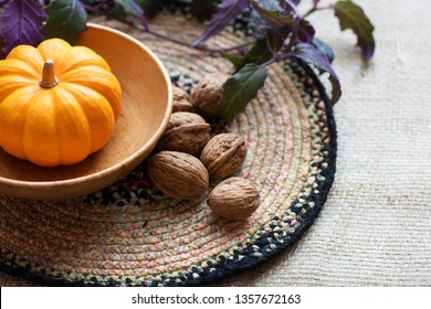 Thanksgiving Fall Still Life with Mini Pumpkin, walnuts and plant as centerpiece on a table with textured fabric tablecloth with copy and text space.  Horizontal with above view