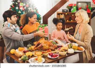 Thanksgiving family on table, giving present box to grandmother