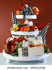 Thanksgiving Farmhouse 3 three tier tray decorated with turkey, stack of books, white and ornage pumpkins, black plaid gnomes and autumn fall leaves. Vertical orientation.