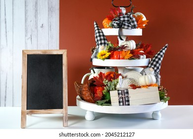 Thanksgiving Farmhouse 3 three tier tray decorated with turkey, stack of books, white and ornage pumpkins, black plaid gnomes and autumn fall leaves. Farmhouse wooden sign board with copy space.
