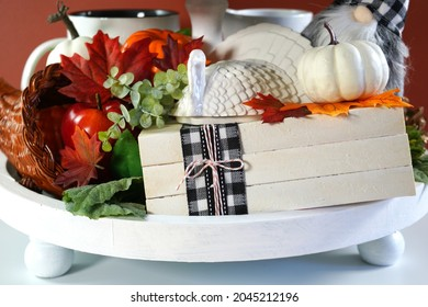Thanksgiving Farmhouse 3 three tier tray decorated with turkey, stack of books, white and ornage pumpkins, black plaid gnomes and autumn fall leaves. Close up on stack of books.