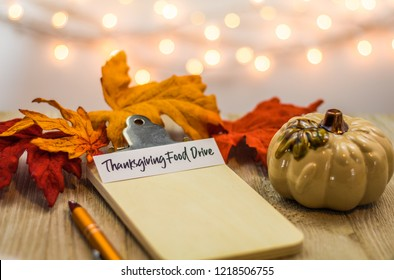 Thanksgiving Food Drive list concept on blank clipboard surrounded with bright leaves and decorative items soft background
