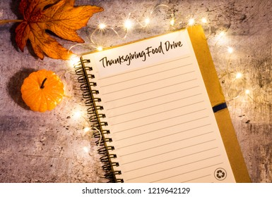 Thanksgiving Food Drive list concept on notebook surrounded with bright leaves and decorative lights, flat lay