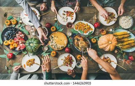 Thanksgiving, Friendsgiving holiday celebration. Flat-lay of friends feasting at Thanksgiving Day table with turkey, pumpkin pie, roasted vegetables, fruit, rose wine, top view