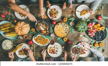 Thanksgiving or Friendsgiving holiday celebration party. Flat-lay of friends feasting at Thanksgiving Day table with turkey, pumpkin pie, roasted vegetables, fruit and rose wine, top view
