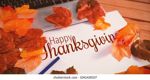 Thanksgiving greeting text against close up of autumn leaves with paper by laptop