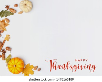 Thanksgiving Greetings. Pumpkins and dry leaves on a white background. Top view.