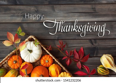 Thanksgiving Greetings. Pumpkins and  leaves in a tray on a dark wooden background. Top view. Flat layer