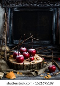 thanksgiving and halloween homemade red caramel glazed taffy apples with sticks on wooden board on sackcloth with tree branches opposite dark concrete wall