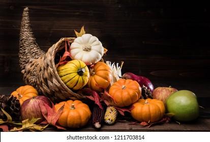 A Thanksgiving holiday decorative cornucopia with pumpkins, squash, leaves etc