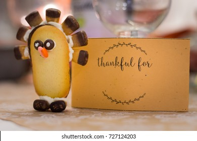 Thanksgiving holiday table place settings made with candy turkeys and gratitude cards.