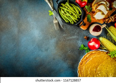 Thanksgiving holiday table with traditional festive food - turkey, pumpkin pie, pumpkins, green beans, cranberry sauce, corn, autumn apples, dark rusty table, top view space for text