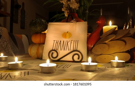 Thanksgiving Holiday Thankful message table decorations with candles, turkey and pumpkins.