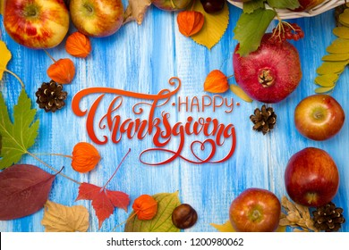 Thanksgiving - letters. Autumn bright background. Flowers, leaves and fruits on a blue wooden background. Background for the autumn holidays and thanksgiving day.