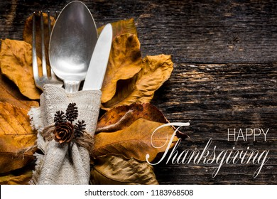 Thanksgiving Meal Setting. Seasonal table setting. Thanksgiving autumn place setting with cutlery and arrangement of colorful fall leaves.