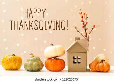 Thanksgiving message with collection of autumn pumpkins with a toy house